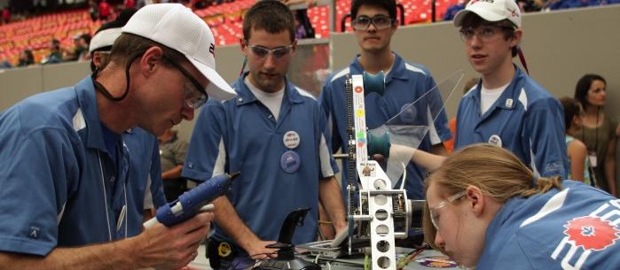 Students and mentors gather around a robot at a competition.